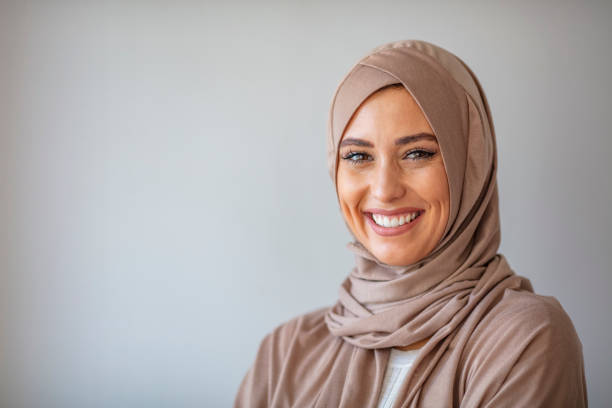 Smiling Muslim Woman Wearing Hijab Portrait of a young woman in traditional Muslim clothing, smiling. Beautiful woman headshot looking at camera and wearing a hijab. Arabian woman with happy smile. Strict formal outfit and elegant appearance. Islamic fashion. religious veil stock pictures, royalty-free photos & images