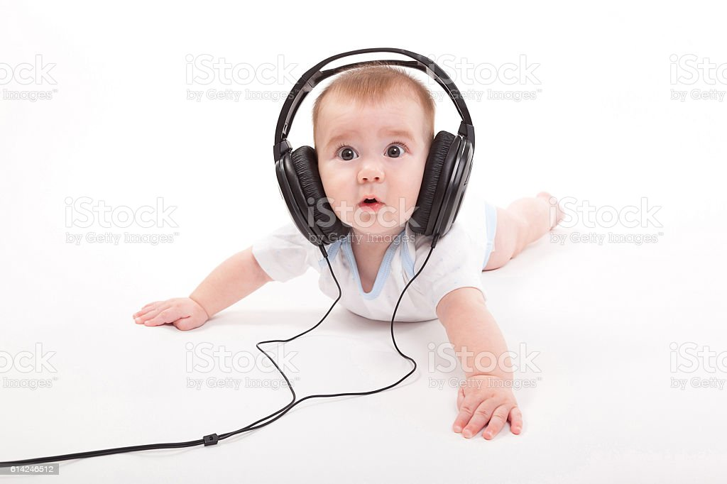 smiling naked baby with headphones on a white background stock photo