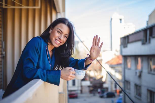 smiling neighbor waving while enjoying a cup of coffee - vizinho imagens e fotografias de stock