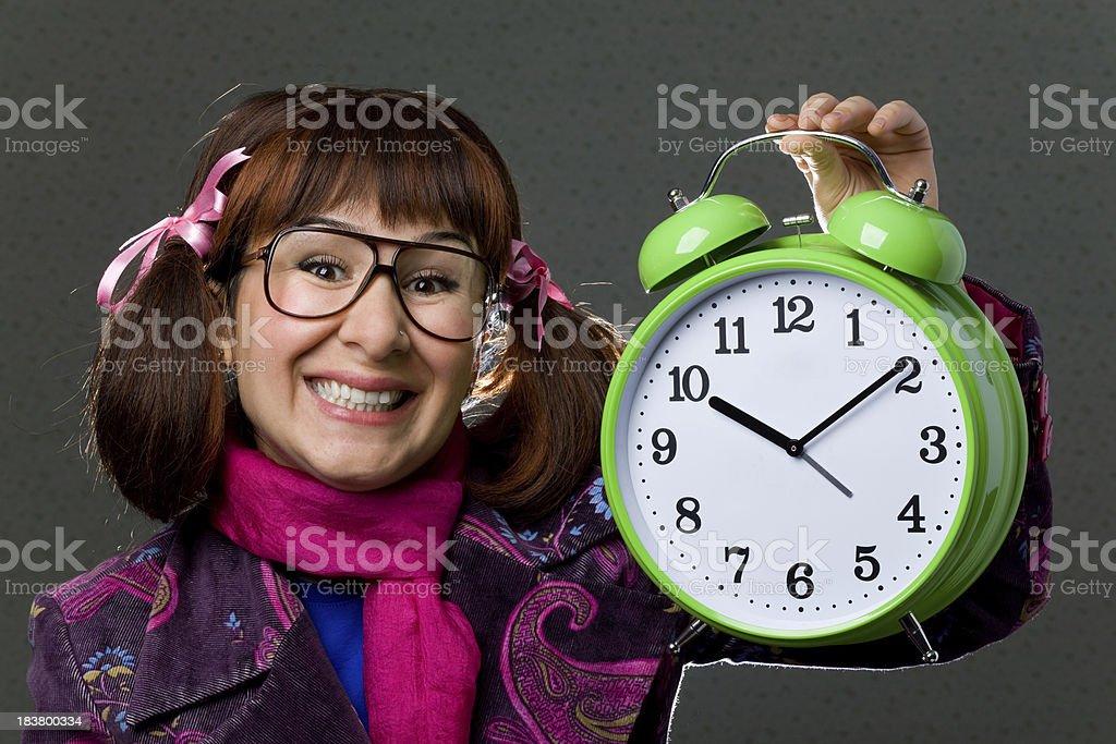 Smiling nerd woman holding alarm clock royalty-free stock photo