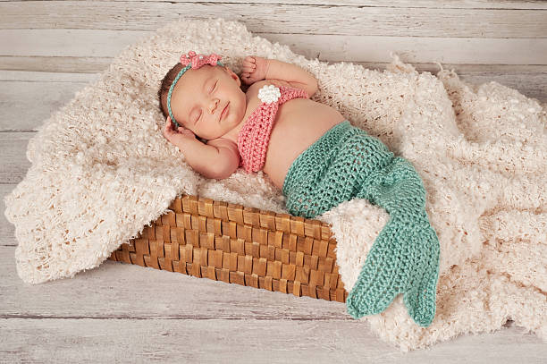 Smiling Newborn Baby Girl in a Mermaid Costume stock photo
