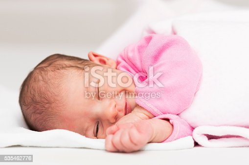 Portrait of a newborn baby girl while sleeping and smiling.