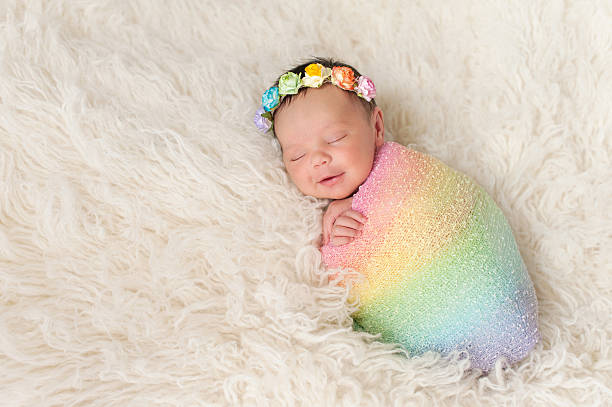 Smiling newborn baby girl wearing a rainbow colored swaddle stock photo