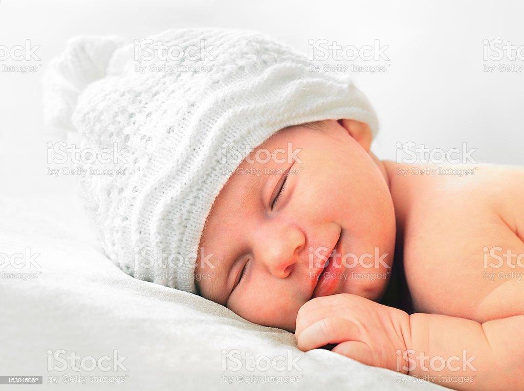 smiling newborn baby in white hat stock photo