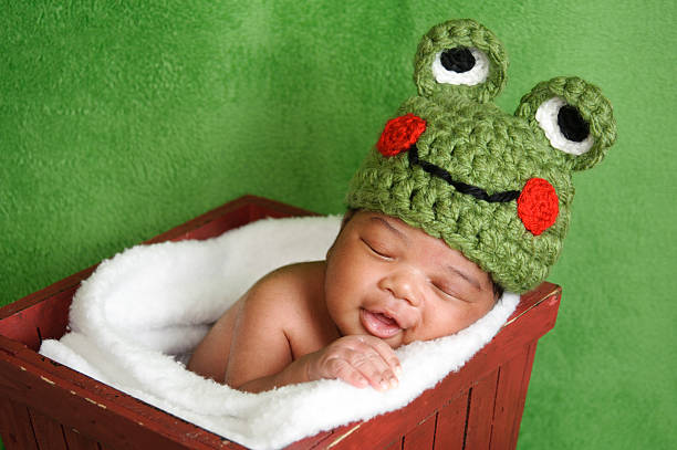 Smiling Newborn Wearing a Frog Hat stock photo