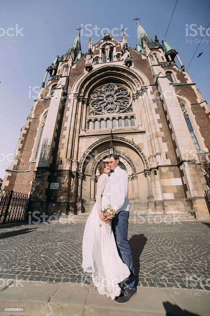 Newlywed couple dancing and hugging near old gothic christian...
