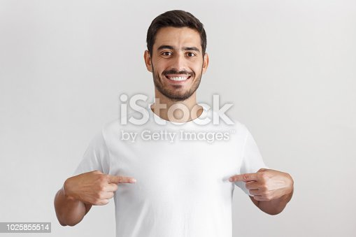 1018069806 istock photo Smiling nice man pointing at blank white t-shirt with both index fingers, copy space for your advertising, isolated on grey background 1025855514
