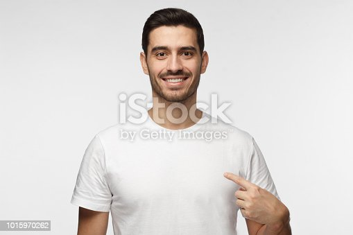 1093999692 istock photo Smiling nice man pointing at his blank white t-shirt with index finger, copy space for your advertising, isolated on grey background 1015970262