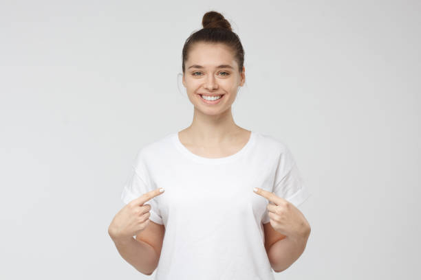 Smiling nice woman pointing at her blank white t-shirt with both index fingers, copy space for your advertising, isolated on grey background stock photo