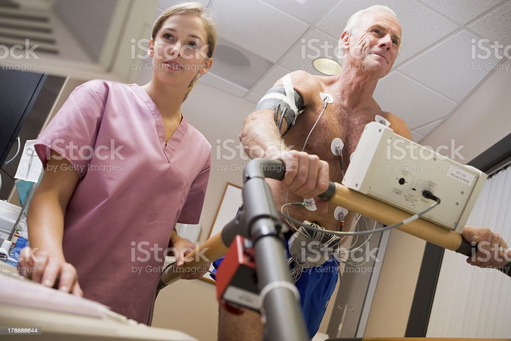 Smiling nurse and man on a treadmill during a check up royalty-free stock photo