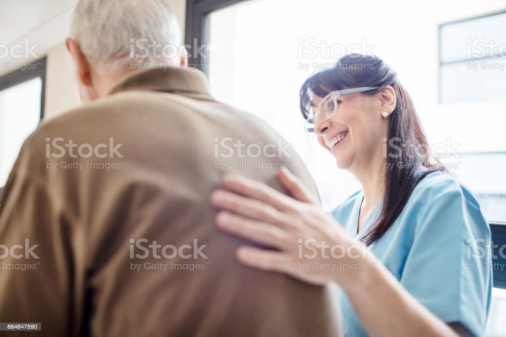 Lächelnde Krankenschwester helfen älteren Menschen im Krankenhaus – Foto