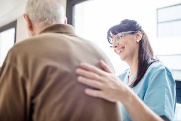 Smiling nurse assisting senior man in hospital stock photo
