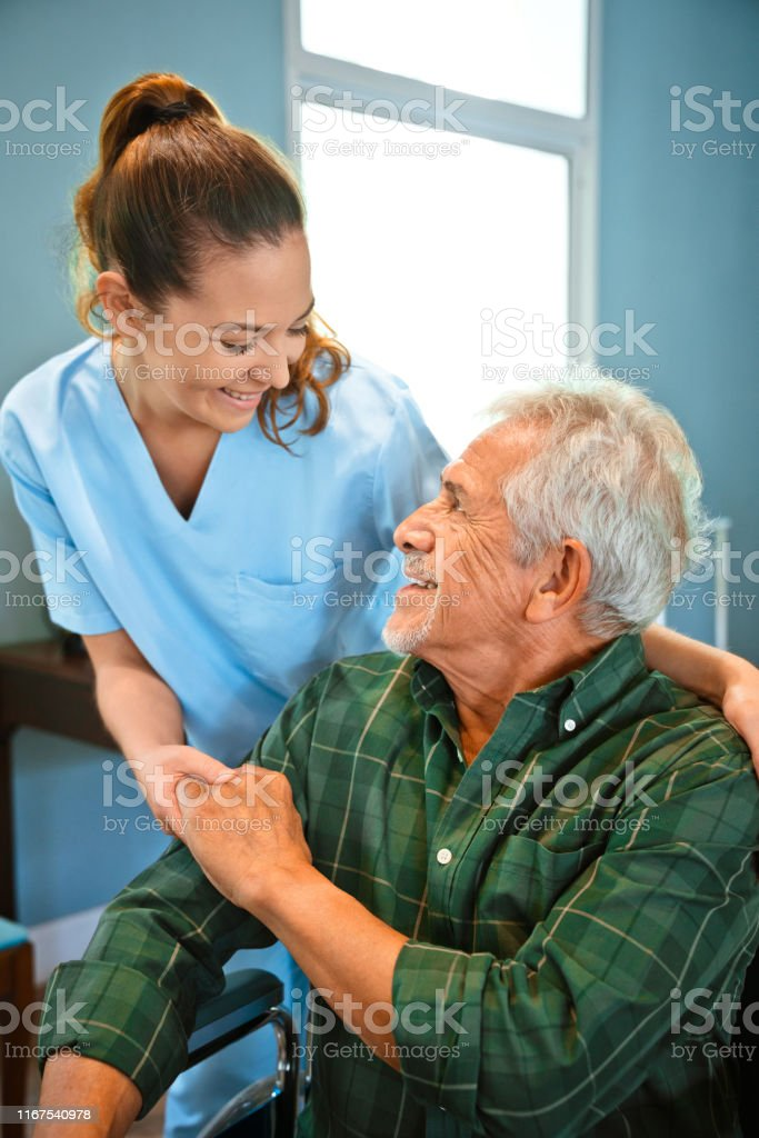 Smiling healthcare worker looking at disabled man holding hands....
