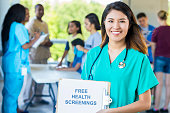 Smiling nurse holding up a ''Free Health Screenings'' sign