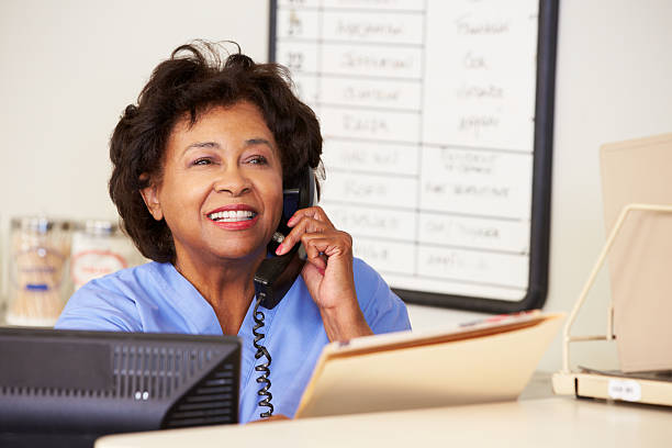 smiling nurse on the phone at nurse station - nurse on phone stock photos and pictures