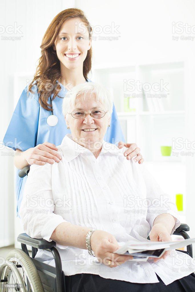 Smiling Nurse Taking Care Of Senior Woman in wheelchair. royalty-free stock photo