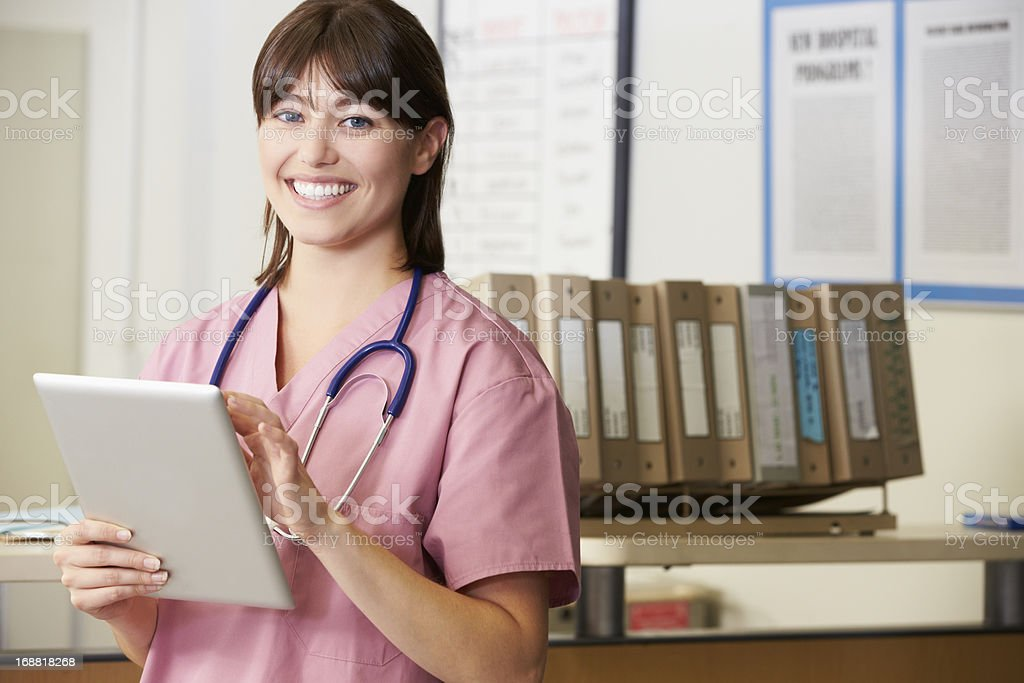 Smiling Nurse using her tablet in front of a row of files stock photo