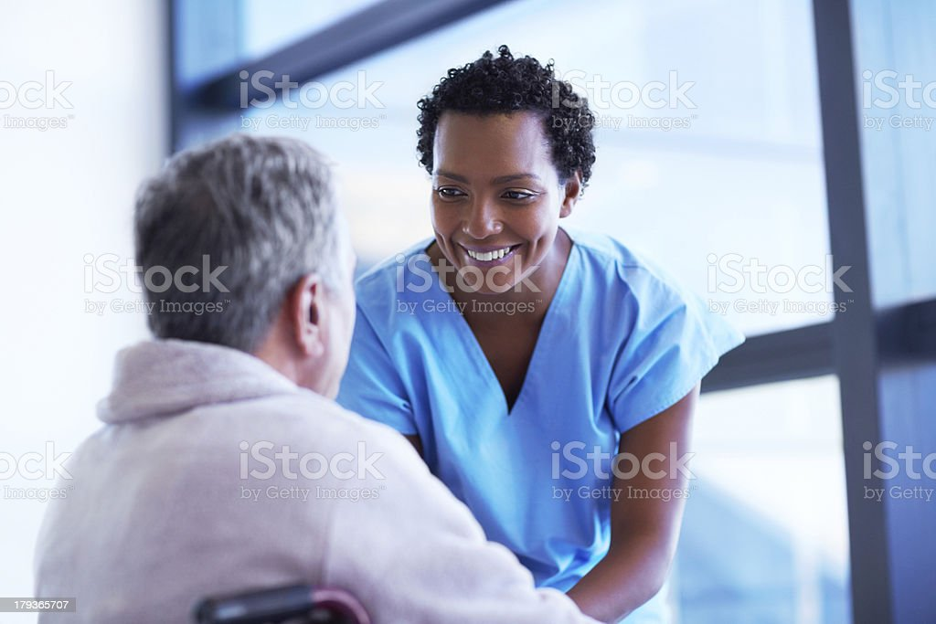Smiling nurse with senior male patient stock photo