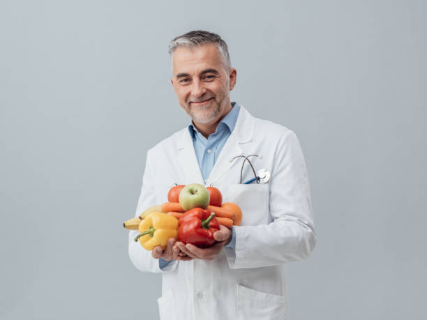 Smiling nutritionist holding fresh vegetables and fruit stock photo