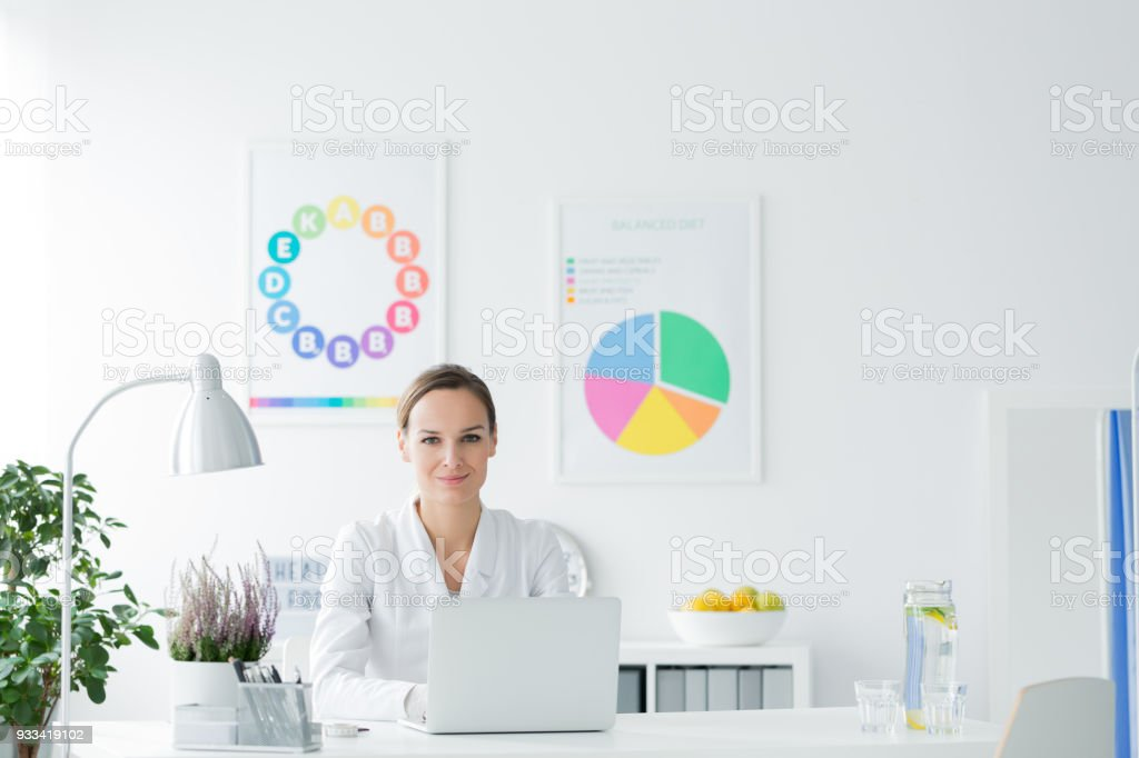 smiling nutritionist in white office royalty free stock photo