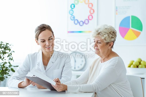 istock Smiling nutritionist showing diet plan 901552090