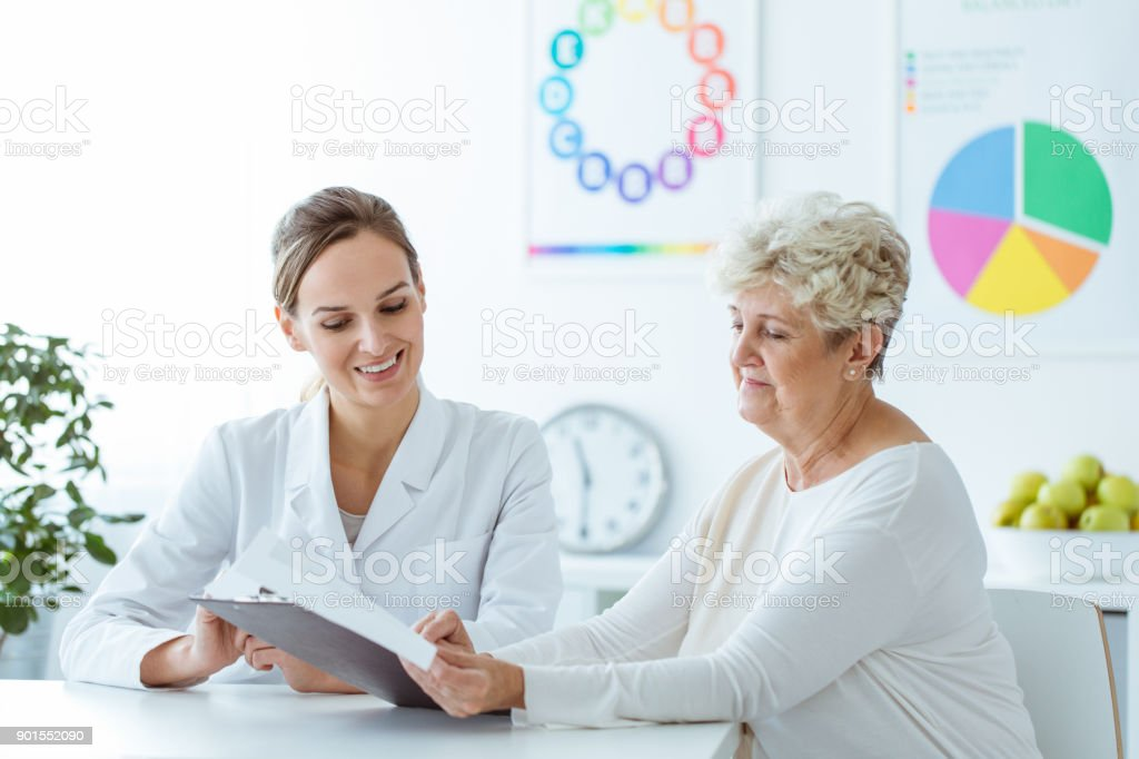 Smiling nutritionist showing diet plan stock photo