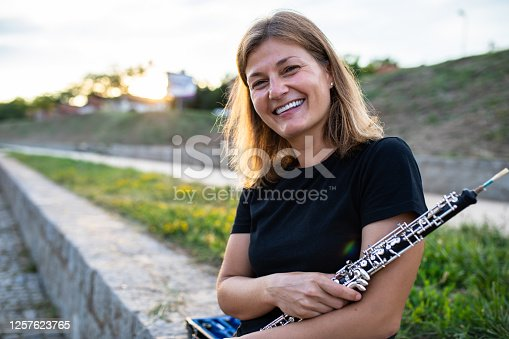A woman is sitting on a stone wall holding an oboe and smiling at sunset