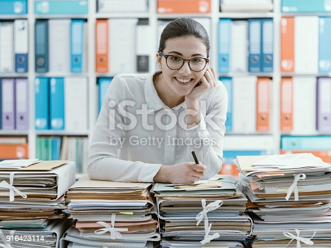istock Smiling office clerk and piles of paperwork 916423114