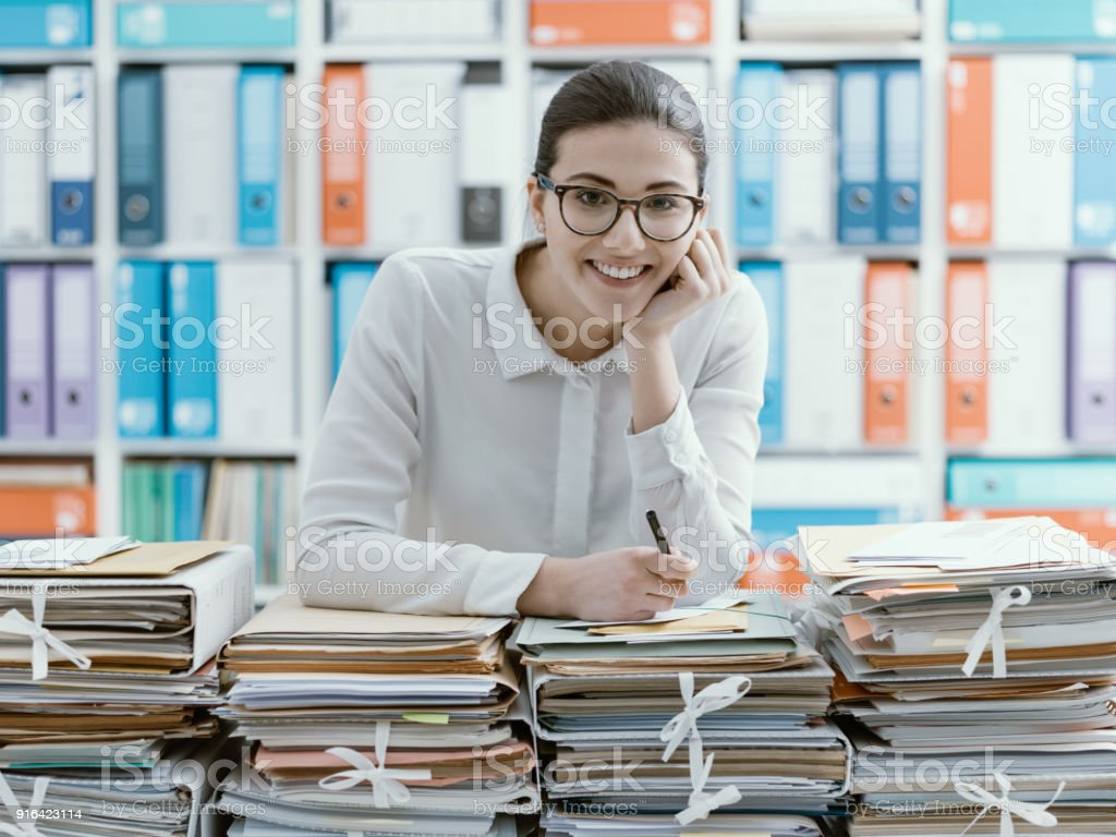 Smiling office clerk and piles of paperwork stock photo