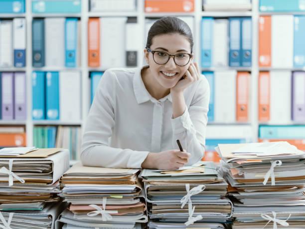 Auxiliar de escritório e pilhas de papelada a sorrir - foto de acervo