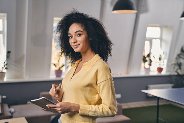 Smiling office worker looking at the camera Waist-up portrait of an attractive woman standing with a diary and pen in her hands entrepreneur stock pictures, royalty-free photos & images