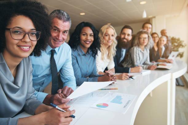 lachende kantoorpersoneel kijken camera in kantoor - grote groep mensen stockfoto's en -beelden
