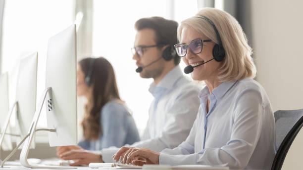 glimlachende oude vrouwelijke call center agent in headset consulting client - dienstverlening stockfoto's en -beelden