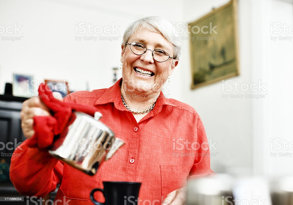 Smiling old lady pours tea or coffee royalty-free stock photo