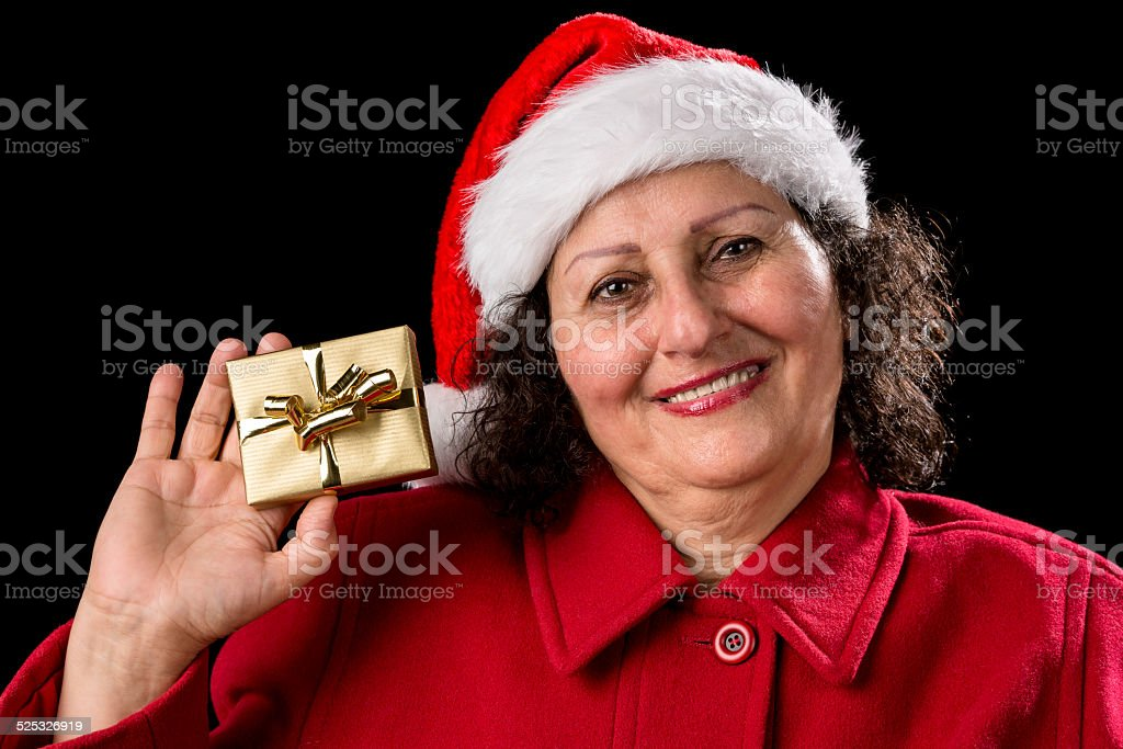 Smiling Old Lady Shows Golden Wrapped Christmas Gift. - Stock image .