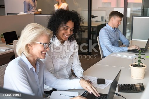 926404274 istock photo Smiling old mentor helping african intern with laptop in office 1146468380