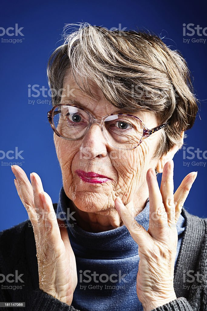 Smiling old woman gestures with both hands royalty-free stock photo