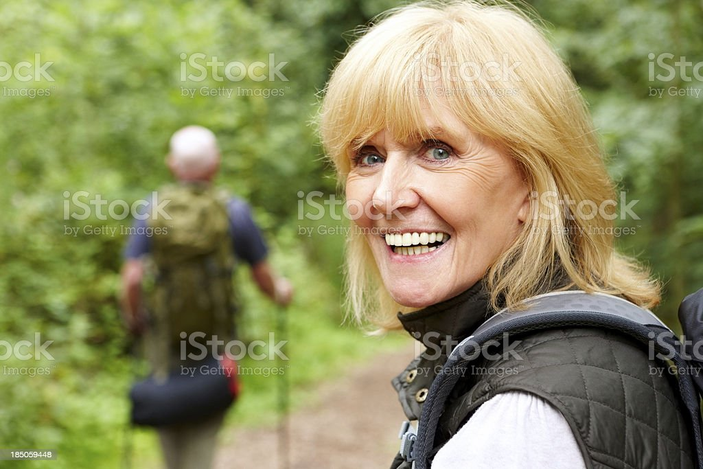 Smiling old woman hiking with a her husband royalty-free stock photo