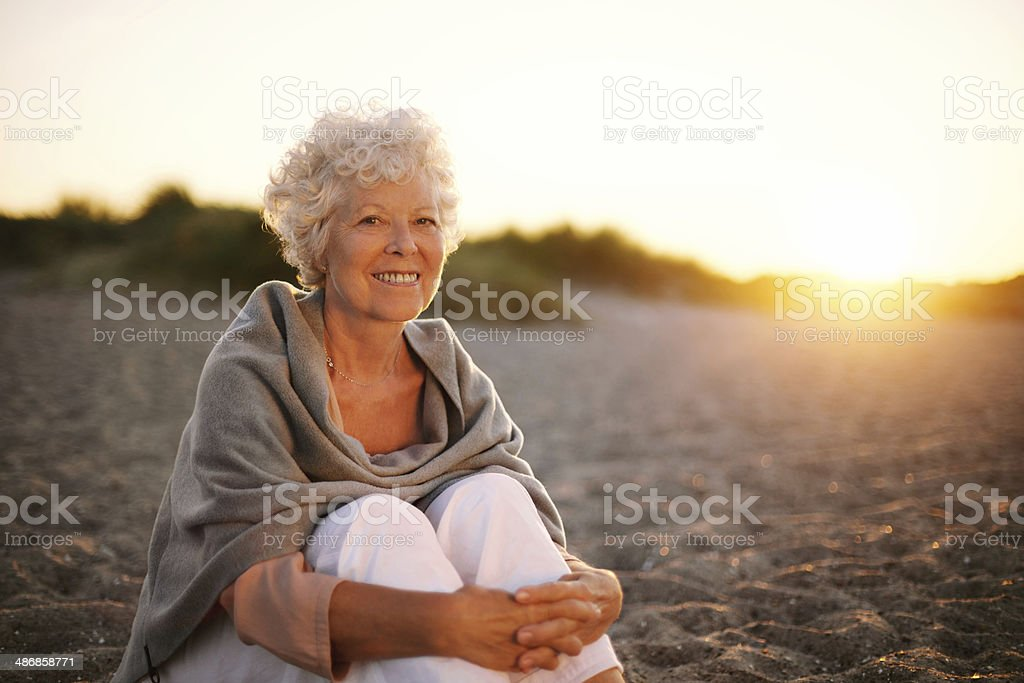 Smiling old woman sitting on the beach stock photo