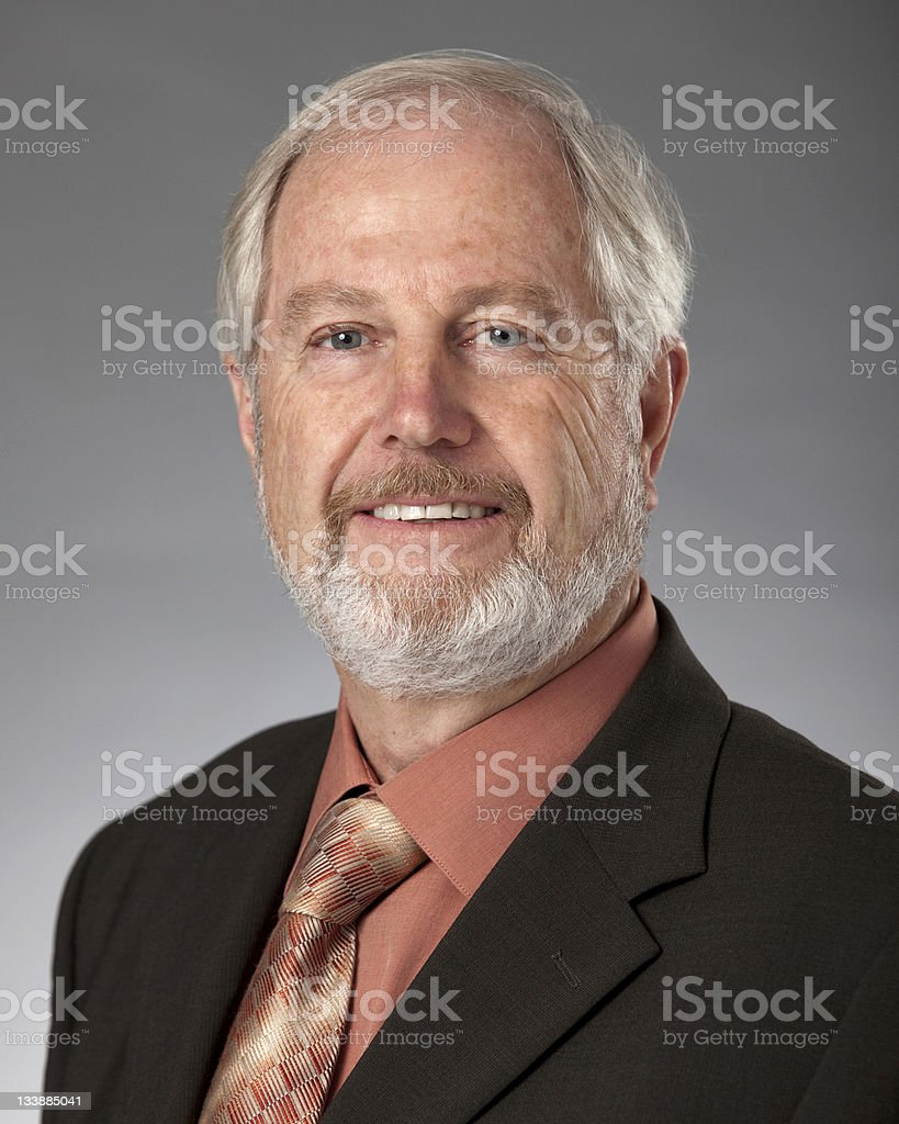 A smiling older businessman in an orange shirt and tie stock photo