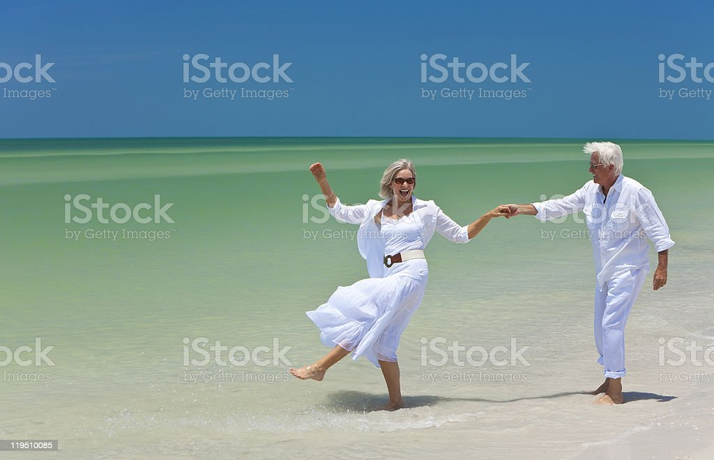 Smiling older couple in white, dancing on a sandy beach royalty-free stock photo