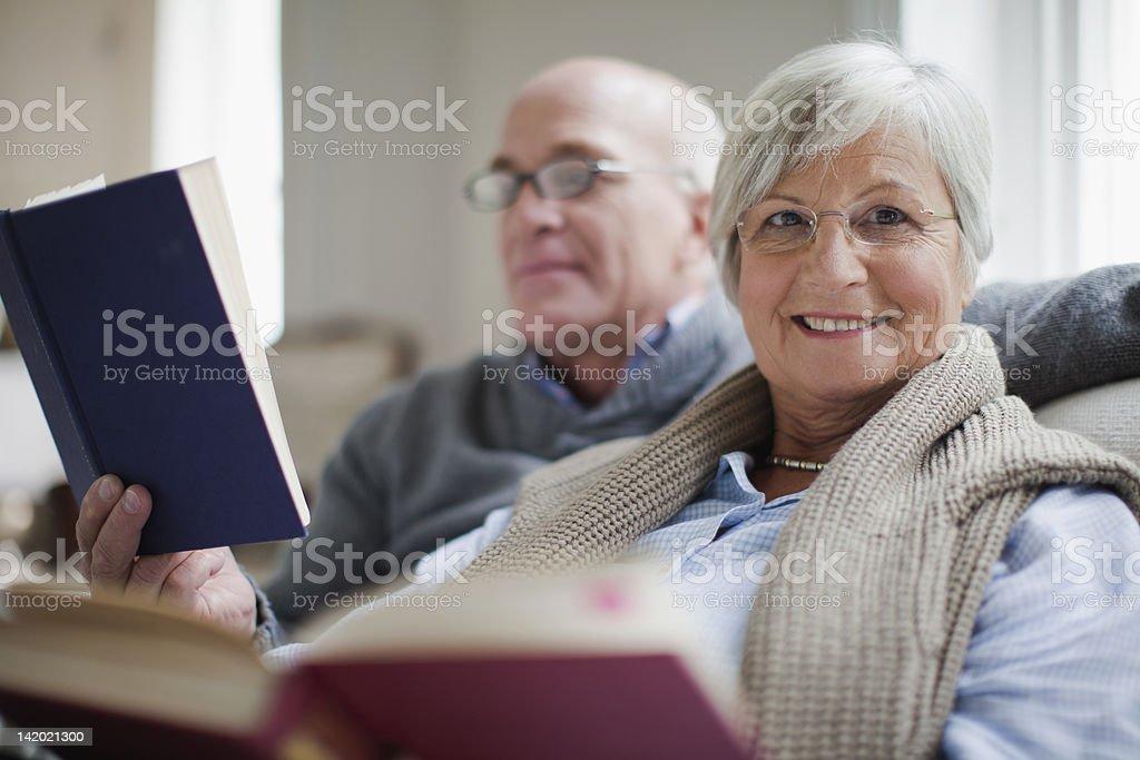 Smiling older couple reading books stock photo