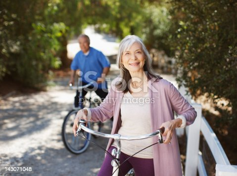 istock Smiling older couple riding bicycles 143071048
