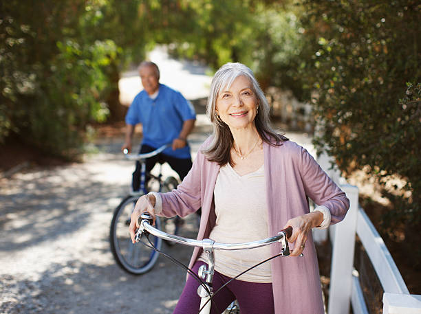 Smiling older couple riding bicycles stock photo