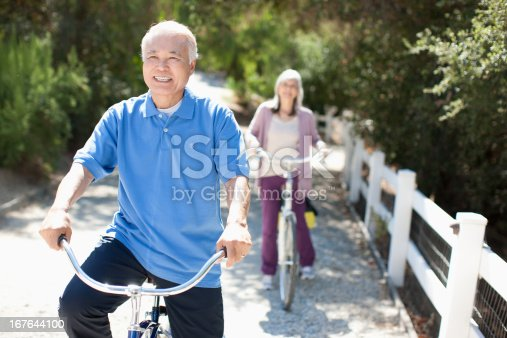 istock Smiling older couple riding bicycles 167644100