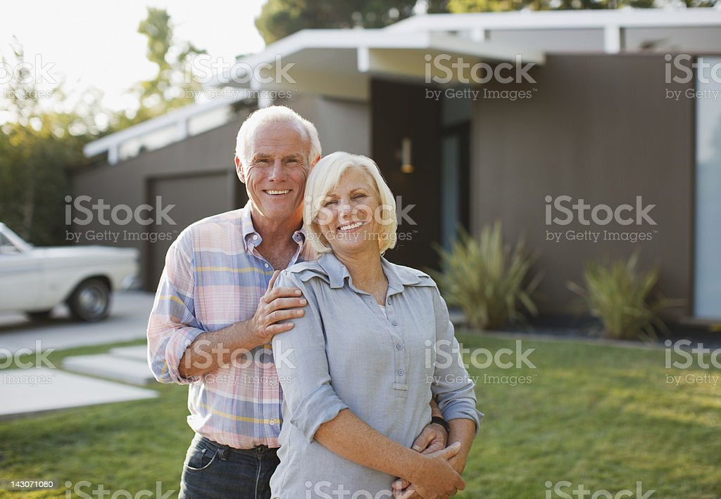 Smiling older couple standing outdoors stock photo