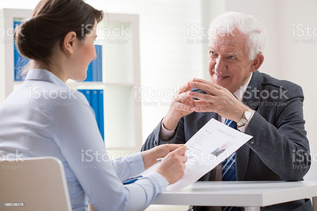 Smiling older man answers questionnaire for young woman stock photo