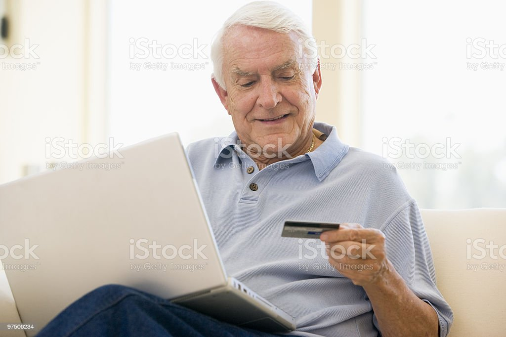 Smiling older man holding credit card while using laptop royalty-free stock photo
