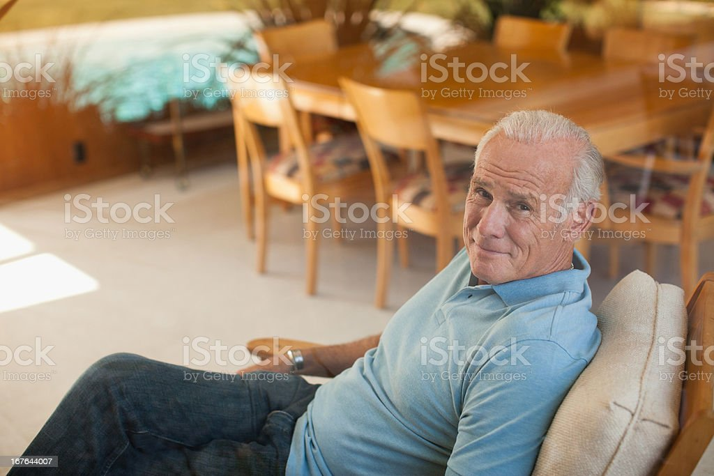 Smiling older man relaxing in armchair royalty-free stock photo