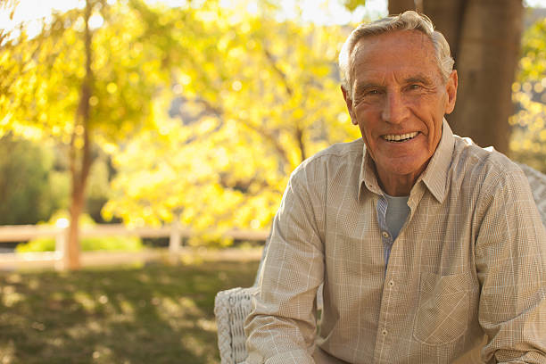 Smiling older man sitting outdoors stock photo